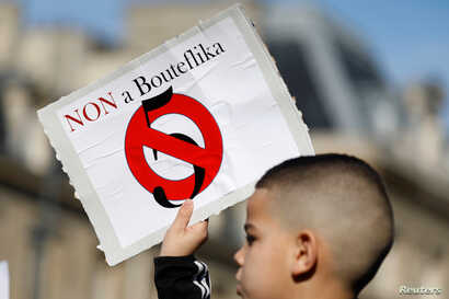 A young boy holds up a placard during a protest against President Abdelaziz Bouteflika seeking a fifth term in a presidential election set for April 18, in Paris, France, Feb. 24, 2019.  Almost 70 percent of Algerians are under 30 years old .