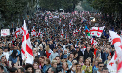 Supporters march during a pre-election rally of the largest opposition party United National Movement in Tbilisi, Georgia, Oct. 5, 2016.
