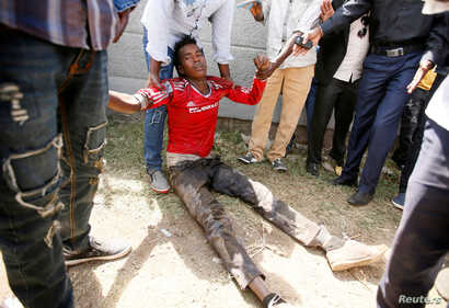 FILE -- People assist an injured protester during Irrechaa, the thanksgiving festival of the Oromo people in Bishoftu town of Oromia region, Ethiopia.