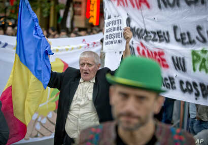 """Romania Canada Gold Mine Protest: FILE -A man holding a banner that reads """"Stop the Rosia Montana siege""""  shouts during a protest in Bucharest, Romania, in this Sunday, Sept. 22, 2013 file photo."""
