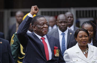 Emmerson Mnangagwa, center, and his wife Auxillia, right, arrive at the presidential inauguration ceremony in Harare, Zimbabwe, Nov. 24, 2017.