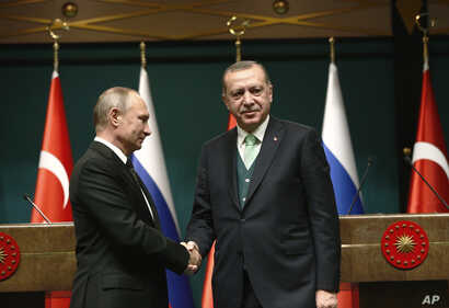 FILE - Turkey's President Recep Tayyip Erdogan, right, shakes hands with Russia's President Vladimir Putin following their joint news statement after their meeting at the Presidential Palace in Ankara, Turkey,  Dec. 11, 2017.