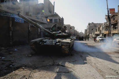 Soldiers loyal to Syria's President Bashar al-Assad are seen at Hujaira town, south of Damascus, after the soldiers took control of it from the rebel fighters, in this handout photograph distributed by Syria's national news agency SANA, Nov. 13, 2013...