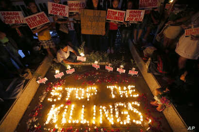"""FILE - human rights activists light candles for the victims of extra-judicial killings around the country in the wake of """"War on Drugs"""" campaign by Philippine President Rodrigo Duterte in suburban Quezon city northeast of Manila, Philippines."""