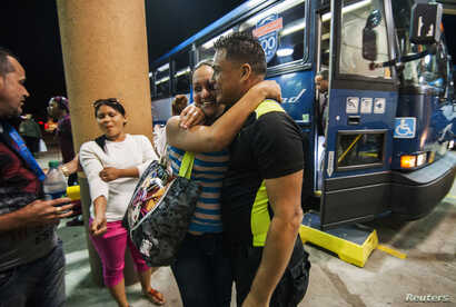 FILE - Cuban migrant Mailin Perez is greeted by her husband Jose Caballero after arriving via Mexico at a bus station in Texas in this 2014 photo.