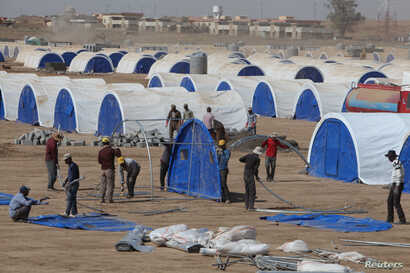 FILE - Workers prepare a tent camp in Khazer west of the Kurdish regional capital Erbil, Iraq, Oct. 11, 2016, for people expected to flee Mosul when the battles for Mosul begins.