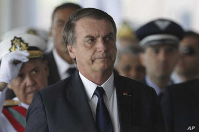 Brazil's President Jair Bolsonaro arrives for the inauguration ceremony of his new naval commander, Ilques Barbosa Junior, at the Naval Club in Brasilia, Jan. 9, 2019.