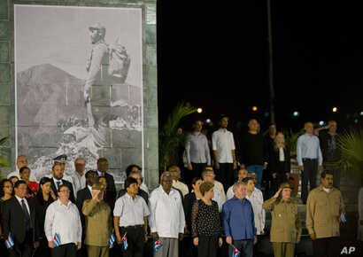 Cuba's President Raul Castro, second from right, salutes during a rally honoring his brother Fidel Castro at Antonio Maceo plaza in Santiago, Dec. 3, 2016.