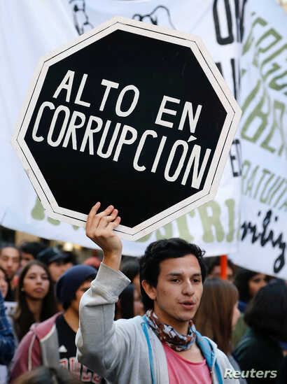 "A demonstrator holds a placard that reads ""High in corruption"" during a rally called by students to protest against government education reforms in Valparaiso city, Chile, June 15, 2016."