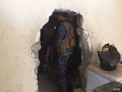 Across West Mosul, homes have holes in the walls that IS militants forced families to make so they could travel from house to house without being seen by airstrikes.  Soldiers now use them in the areas they've captured to avoid IS snipers on June 23...