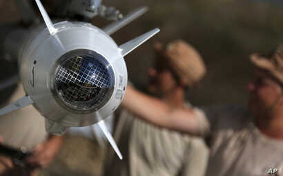 In this photo taken from Russian Defense Ministry official web site on Tuesday, Oct. 6, 2015,  Russian military support crew inspect missiles attached to their jet at an air base in Syria. at an air base Hmeimim in Syria.