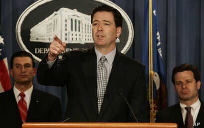 FILE - Deputy Attorney General James B. Comey, center, gestures during a news conference at the Department of Justice in Washington, April 12, 2005. Behind Comey are prosecutor George Z. Toscas, left, and Assistant Attorney General Christopher Wray.