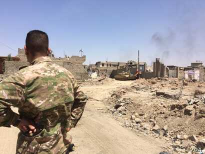 An Iraqi soldier overlooks airstrikes and car bombs in IS's last stronghold, Mosul's Old City on June 18, 2017 in Mosul, Iraq (H.Murdock/VOA)