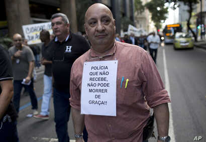 A police officer carries a sign that states in Portuguese that unpaid police can't risk their lives in the line of duty, in Rio de Janeiro, Brazil, June 27, 2016.