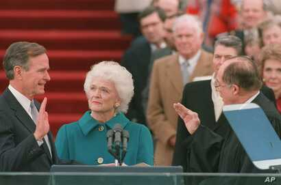 President George Bush raises his right hand as he is sworn into office as the 41st president of the United States by Chief Justice William Rehnquist outside the west front of the Capitol on Jan. 20, 1989.