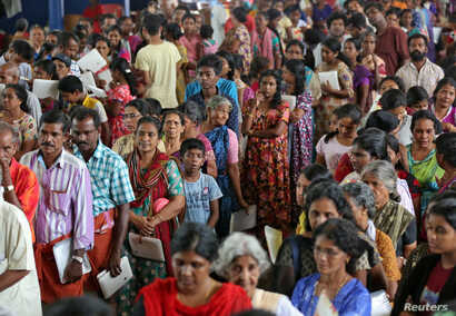 Flood-affected people wait to receive food inside a college auditorium, which has been converted into a temporary relief camp, in Kochi in the southern state of Kerala, India, Aug. 20, 2018.