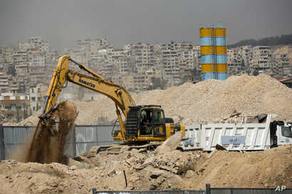 FILE - Heavy equipment works at a building site in southwestern Damascus, Syria, Oct. 8, 2018.