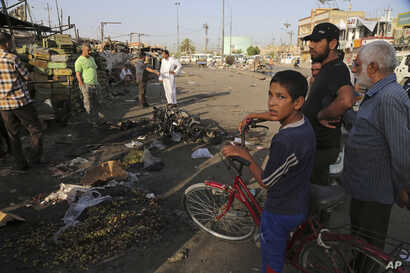 Iraqi civilians gather the morning after a car bombing that killed many people and wounded tens of others in a crowded outdoor market, in the Shiite neighbourhood known as Sadr City, Baghad Iraq, Wednesday, July 16, 2014. (AP Photo/Karim Kadim)