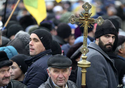 A man holds an Orthodox cross as people support an independent Ukrainian church near the St. Sophia Cathedral in Kyiv, Ukraine, Dec. 15, 2018.