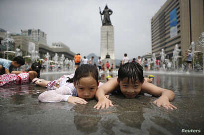 Children play in a fountain to cool down on a hot summer day in front of the General Lee Soon-shin statue in Gwanghwamun, Seoul July 28, 2014.