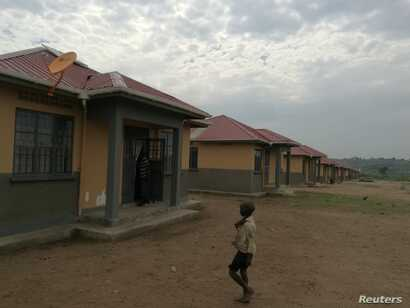A boy walks past a row of houses in Kyakaboga resettlement village in Hoima District, Uganda, July 14, 2018.