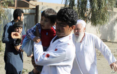 Men carry children away from an explosion site in Lashkar Gah, capital of southern Helmand province, Afghanistan, Feb. 24, 2018.