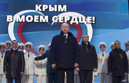 "Russian President Vladimir Putin, with leaders of newly-annexed Crimea in the background, is seen at a rally in Moscow, March 18, 2014. The sign in the back reads ""Crimea is in my heart!"""