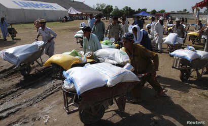 FILE - People fleeing from the military offensive against Pakistani militants in North Waziristan walk away with wheelbarrows of relief handouts from the World Food Program at a distribution point for internally displaced persons in Bannu, located in...