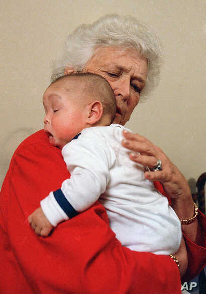 FILE - In this March 22, 1989 file photo, first lady Barbara Bush holds an infant identified as Donavan during a visit to Grandma's House in Washington. Grandma's House serves as a house for infants and small children infected with the AIDS virus.