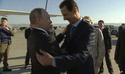 FILE - In this Dec. 11, 2017, frame grab made available by Russian Presidential TV Syrian President Bashar al-Assad, right, greets Russian President Vladimir Putin upon his arrival to the Hemeimeem air base in Syria.