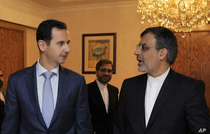 Syrian President Bashar Assad (left), meets with Iranian Deputy Foreign Minister for Arab-African Affairs Hossein Jaberi Ansari in Damascus, Syria, Thursday, Dec. 22, 2016.