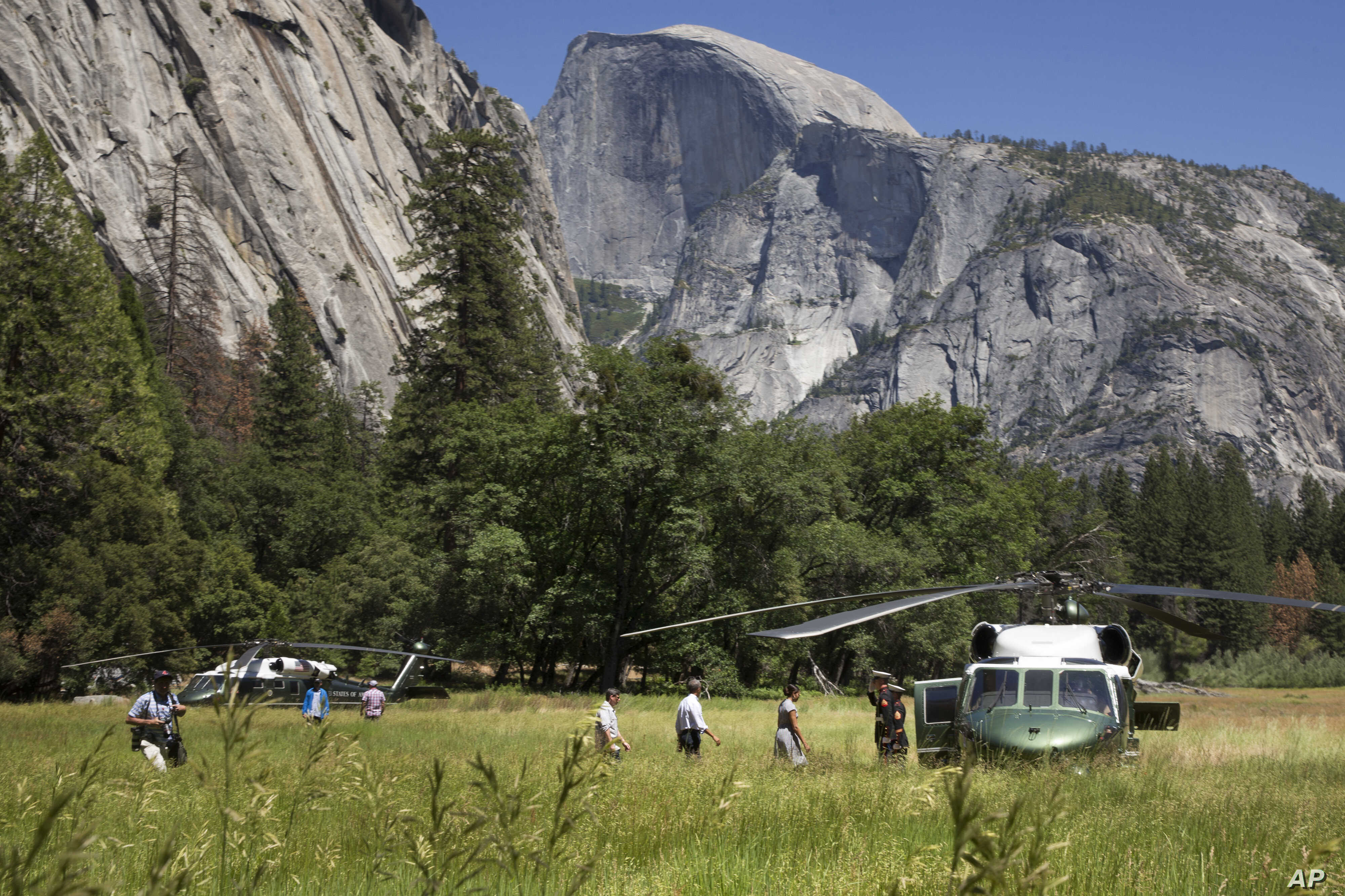 President Barack Obama, center, and first lady Michelle Obama follow their daughters to board the Marine One helicopter in a meadow to leave Yosemite National Park, on Sunday, June 19, 2016, after visiting the park to celebrate the 100th anniversary ...