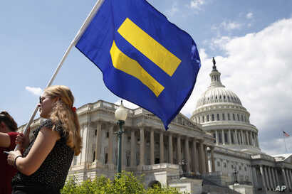 "A supporter of LGBT rights holds up an ""equality flag"" on Capitol Hill in Washington, July 26, 2017, during an event held by Rep. Joe Kennedy, D-Mass., in support of transgender members of the military, in response to President Donald Trump's declara"