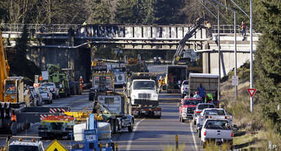 Vehicles fill the highway at the scene of Monday's Amtrak train crash onto Interstate 5 from the railroad bridge above, Dec. 20, 2017, in DuPont, Wash.