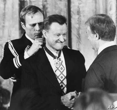 President Carter shakes hands with his national security adviser, Zbigniew Brzezinski, as he presents Brzezinski with the Medal of Freedom at a White House ceremony, Jan. 17, 1981, in Washington.