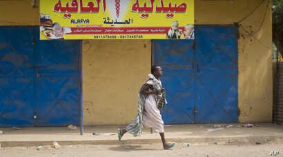 A young woman runs through the street as gunshots ring out a few streets over, in Malakal, Upper Nile State, in South Sudan.