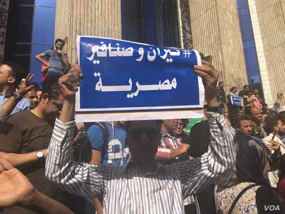 "An Egyptian protester holds a sign saying in Arabic ""Tiran and Sanafir are Egyptian,"" referring to Red Sea islands Egypt plans to cede control of to Saudi Arabia in downtown Cairo, April 15, 2016. (VOA/ H. Elrasam)"