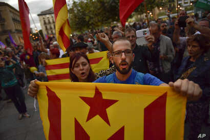 "Pro-independence supporters hold up ""esteleda"" or pro-independence flags and shout slogans as they walk along the street during a demonstration in Pamplona, Spain, Oct. 3, 2017, protesting against the use of force by police."