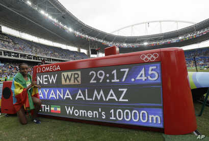 Ethiopia's Almaz Ayana poses next to a scoreboard showing her new world record in the women's 10,000-meter final during the Summer Olympics in Rio de Janeiro, Brazil, Friday, Aug. 12, 2016.