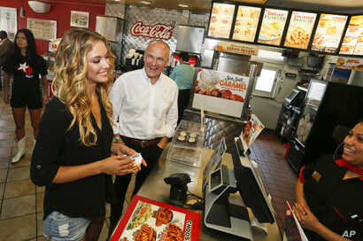 Sports Illustrated swimsuit model Hannah Ferguson, left, orders lunch along side CKE Restaurants CEO Andy Puzder after a news conference on Aug. 6, 2014 in Austin, Texas