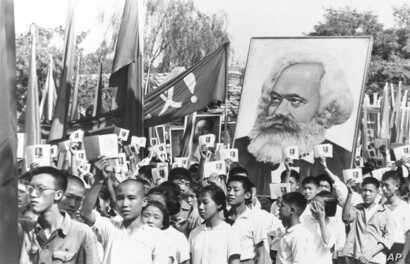 FILE - In this file photo taken Sept. 14, 1966, youths are seen at a rally during the height of the Red Guard upheaval waving copies of the collected writings of Communist Party Chairman Mao Zedong, often referred to as Mao's Little Red Book and carr...