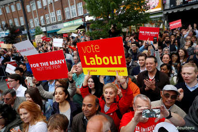 Supporters watch Jeremy Corbyn the leader of Britain's opposition Labour Party, as he speaks at an election campaign event in Harrow, June 7, 2017.