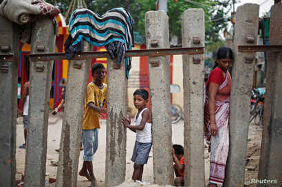 Children play as a woman crosses a railway fence at a slum area in New Delhi, India, July 11, 2018.