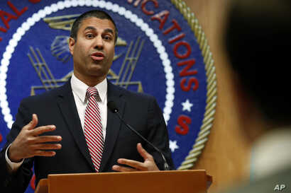 FILE - Federal Communications Commission Chairman Ajit Pai answers a question from a reporter after a meeting where commissioners voted to end net neutrality, in Washington, Dec. 14, 2017.