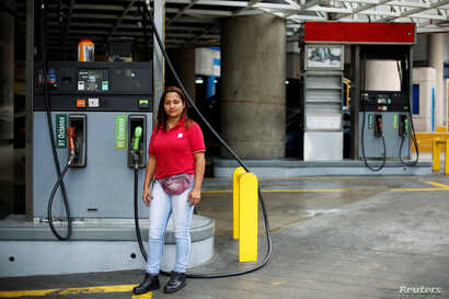 Yanis Reina, 30, a gas station attendant, poses for a photograph at a gas station in Caracas, Venezuela, Feb. 24, 2017.