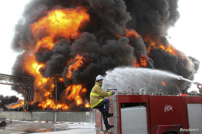 A Palestinian firefighter works during efforts to extinguish a fire at Gaza's main power plant, which witnesses said was hit in Israeli shelling, in the central Gaza Strip, July 29, 2014.