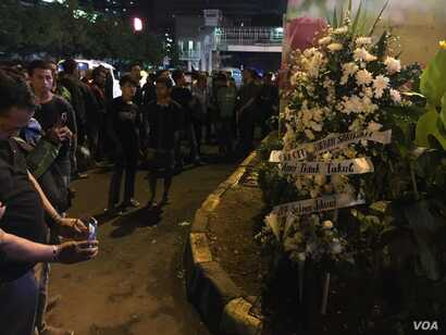 Crowds mill around an informal memorial near the attack site, 12 hours after the bombing, Jakarta, Indonesia, Jan. 14, 2016. (VOA/S. Herman)