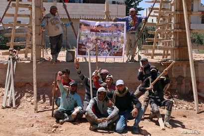 """Members of """"You Destroy and We Rebuild Brigade"""" pose at a construction site in front of their banner depicting a still from their parody video that circulated on Syrian social media, in the rebel-held town of Saida, in Deraa province, Syria, May 24,..."""