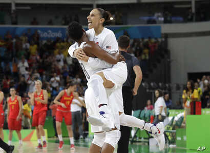 United States' Diana Taurasi, right, leaps into the arms of teammate Angel McCoughtry as they celebrate their win over Spain in a women's gold medal basketball game at the 2016 Summer Olympics in Rio de Janeiro, Brazil, Aug. 20, 2016.