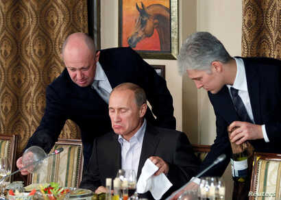 FILE - Evgeny Prigozhin (L) assists then-Russian Prime Minister Vladimir Putin during a dinner at Cheval Blanc restaurant on the premises of an equestrian complex outside Moscow, Russia, Nov. 11, 2011.